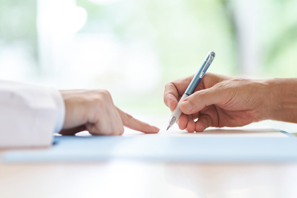 Person signing a contract with clinician at desk